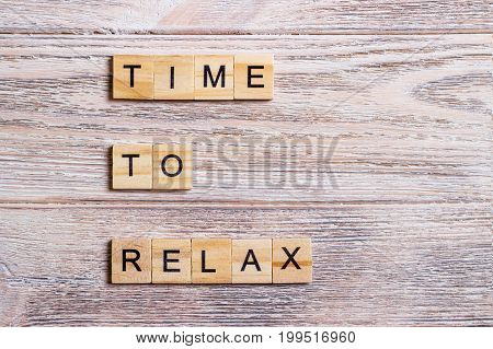 time to relax text on wooden cubes on a wooden background
