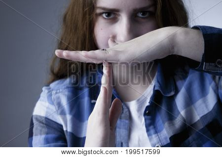 Young beautiful woman showing time out hand sign gesture (Body language gestures psychology)