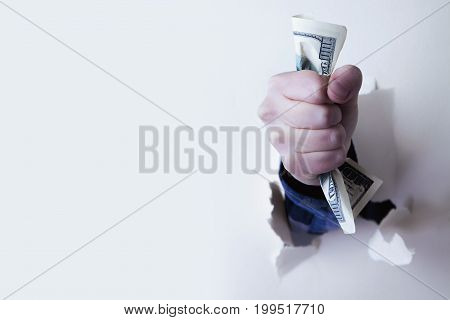 Fist full of paper money dollars punching through a wall. (Wealth earnings victory domination finance concept)