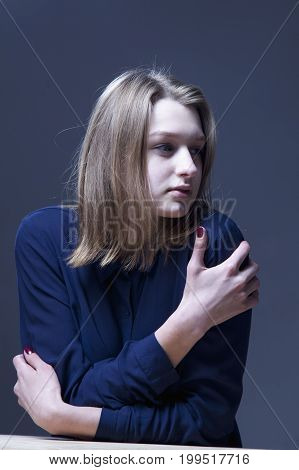 Folded hands of the girl as a symbol of loneliness. (Body language gestures body psychology)