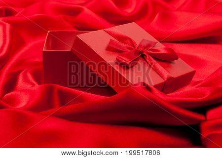 Open fancy box on luxurious red silk