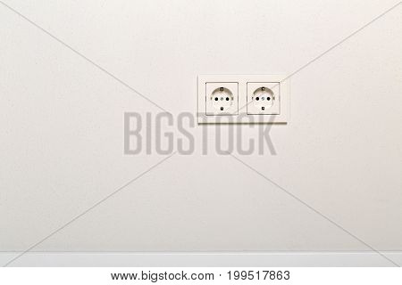 Empty unplugged european wall outlet on white plaster wall with copy space