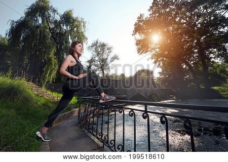 Side view of determined sportswoman looking forward while warming up in sunlight. Fitness woman. Fitness woman in the city park. Caucasian female fitness model working out in the morning