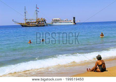 July, 2017 - Vacationers bathe in the sea and sunbathe in the sun on Cleopatra Beach (Alanya, Turkey).