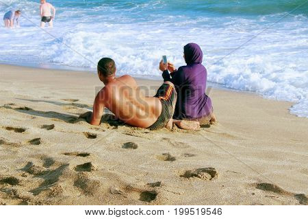 July, 2017 - A young Muslim married couple makes a selfie on Cleopatra Beach (Alanya, Turkey).