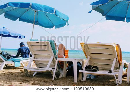 July, 2017 - People rest on deckchairs in the shade of beach umbrellas on Cleopatra Beach (Alanya, Turkey).