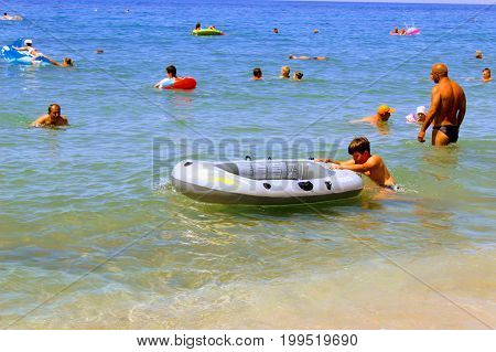July, 2017 - The boy pushes ahead a rubber boat in the water on Cleopatra Beach (Alanya, Turkey).