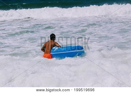 July, 2017 - A tanned man with a large inflatable blue circle for swimming comes into the sea (Alanya, Turkey).