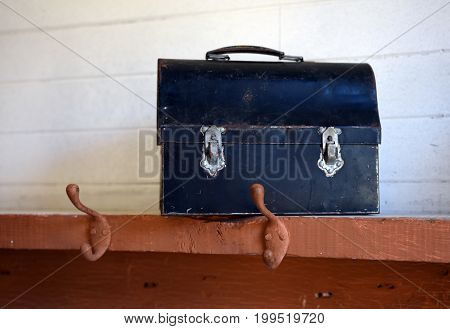 An image of a old antique lunch box on a shelf.