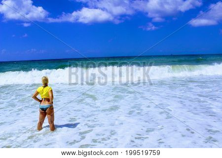 July, 2017 - A woman in a yellow jersey is standing on the seashore at Cleopatra Beach (Alanya, Turkey).