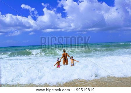 July, 2017 - A woman with two children bathing in the surf on the seashore at Cleopatra Beach (Alanya, Turkey).