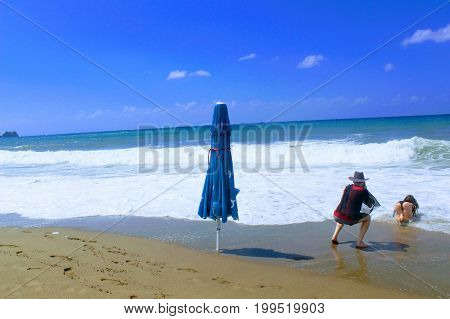 July, 2017 - A closed beach umbrella stands in the surf zone on Cleopatra Beach (Alanya, Turkey).