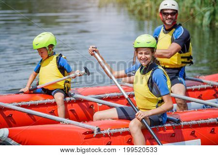 Happy girl with her father and brother wearing life vests and helmets on the catamaran.