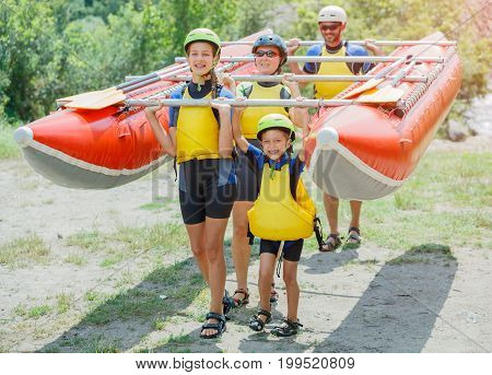 Ready for rafting. Happy family of four wearing life vests and helmets on the catamaran. Rafting family on holidays