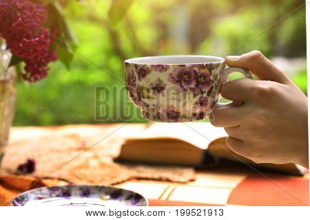 hand hold cup of tea with lilac bouquet in vase and book on summer flower garden background