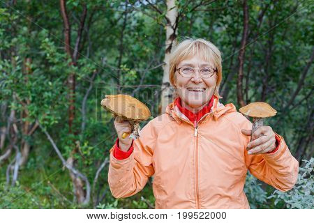 Happy active older woman - mushroom picker, inhale the smell of white mushrooms found it.