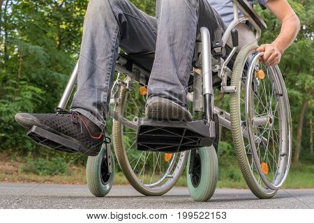 Legs Of Handicapped Or Disabled Man On Wheelchair.