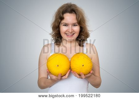 Young Beautiful Woman Holds Melons In Hands Above Her Breast. Pl