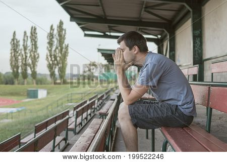 Despair And Depressed Man Is Sitting On Bench At Stadium.