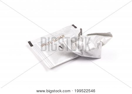 Intact and crumpled packaging of white sugar. Isolated white background. Concept of cutting down sugar intake.