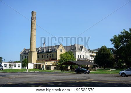 JOLIET, ILLINOIS / UNITED STATES - JULY 17, 2017: An old brick smokestack, no longer in use, towers over the other buildings at the University of Saint Francis in Joliet, Illinois.