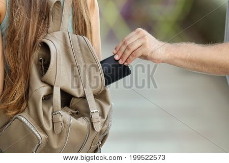Close up of a thief hand stealing a phone from a bag on the street
