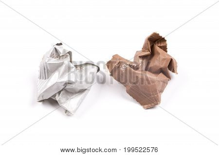 Crumpled packaging of white and brown sugar. Isolated white background. Concept of cutting down sugar intake.