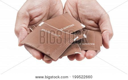 Hand filled with brown sugar packs. Isolated on white background.