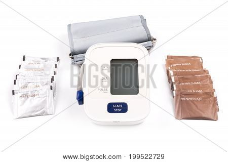 Brown and white sugar packs and blood pressure monitor isolated on a white background