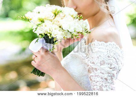 Bouquet in bride's hands. Bride with a wedding bouquet in the summer park. Woman with a bouquet.
