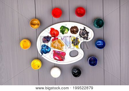 Top view of palette and set of open cans of colored paints on the grey wooden background