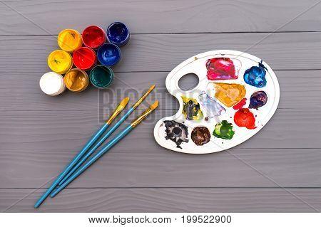 Top view of palette and set of open cans of colored paints with brushes on the grey wooden background