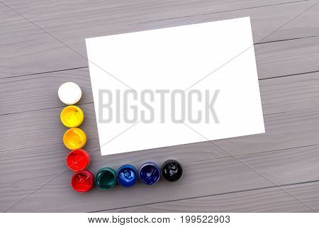 Top view of open cans of colored paints and sheet of paper on the grey wooden background
