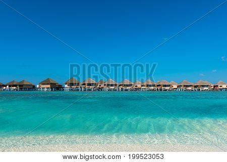 Horizontal picture of turquoise water with bungalows during a sunny day in Maldives