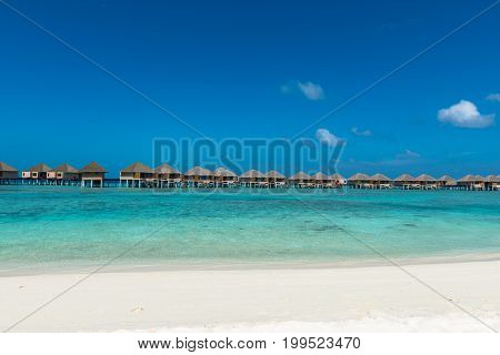 Panorama picture of turquoise water with bungalows during a sunny day in Maldives