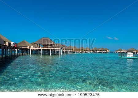 Panorama picture of turquoise water with bungalows during a sunny day in Maldives. Blue sky.