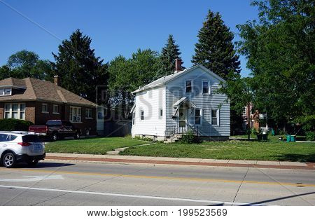 JOLIET, ILLINOIS / UNITED STATES - JULY 18, 2017: A small white two story single family home, on Plainfield Road in Joliet.