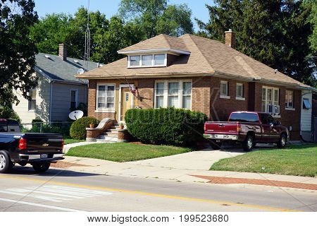 JOLIET, ILLINOIS / UNITED STATES - JULY 18, 2017: A brown brick single family home, with a driveway, on Plainfield Road, in Joliet.