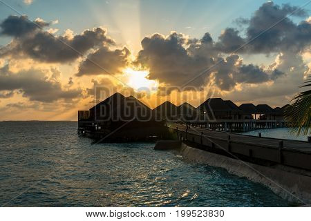 Horizontal picture of yellow beautiful sunset over bungalows with cloudy sky in Maldives.