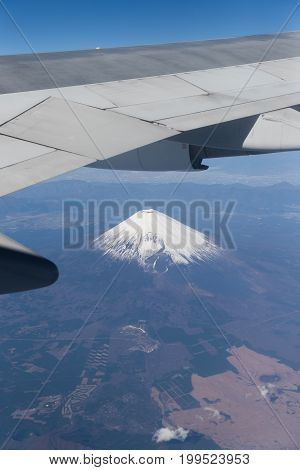 Top of Mountain Fuji with snow in winter season taken from on airplane after takeoff from Tokyo Haneda international airport