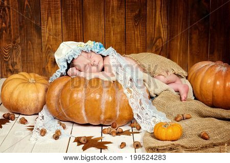 Tale of Cinderella. Little beautiful newborn baby girl in a bonnet sleeping on a pumpkin.