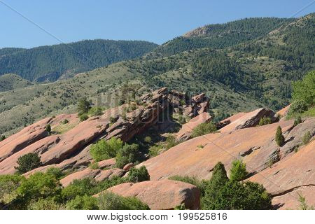 Summer view of geological rock formations in Red Rocks Park Colorado with background of Rocky Mountain foothills