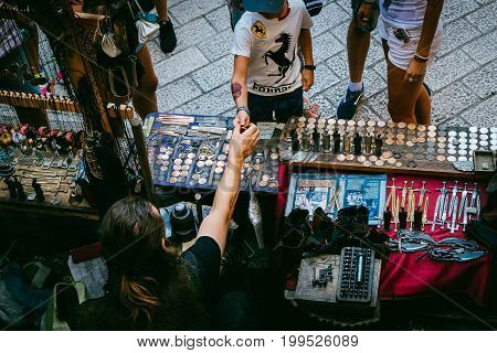 Dubrovnik Croatia - July 17 2017: Merchant selling handmade antique souvenir to a child in Dubrovnik 's street market. Dubrovnik is one of the most famous travel destination in Croatia.
