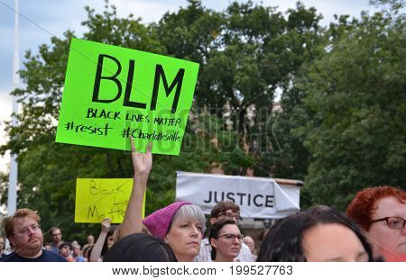 ANN ARBOR MI - AUG 13: A woman holds up a sign at a rally in solidarity with the counter-protesters of Charlottesville in Ann Arbor MI on August 13 2017.