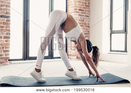 Young beautiful girl wearing fashion sports wear doing exercise on mat at loft gym