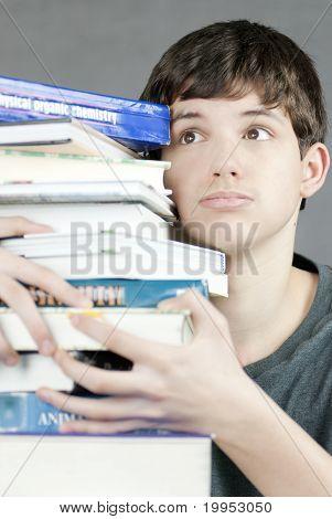 Overwhelmed Teen Holds Stack Of Textbooks