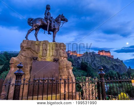 Royal Scots Greys Monument with Edinburgh Castle in the background at night from Princes Street.