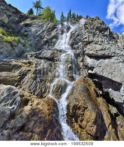 Summer mountain landscape of Shirlak waterfall in rocks of Altai mountains at bright sunny day with white clouds on a blue sky Altay Republic Siberia Russia.
