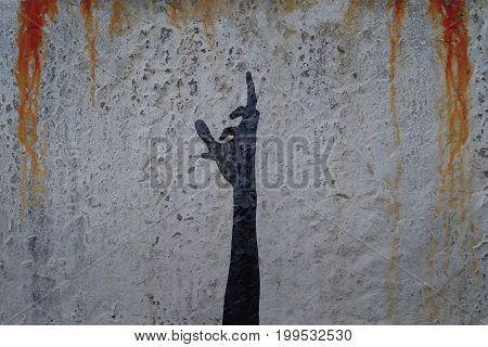 Shadow of human hand on cement wall with blood drops background. Halloween theme illustration.