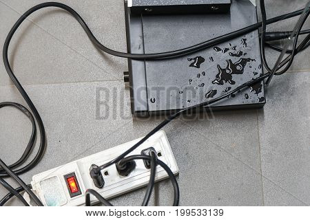 Electrical appliances and wires are wet on the floor.
